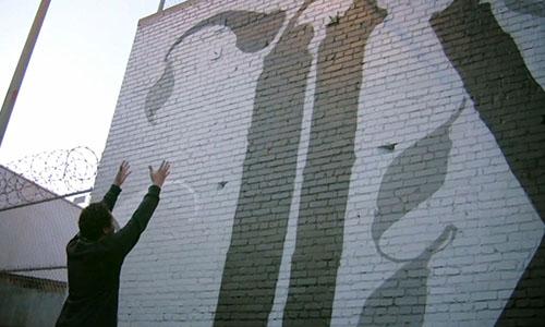 Filmszene aus After the Violence - Künster steht vor Graffitiwand